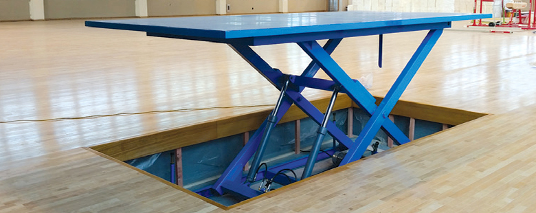 blue scissor lift coming out of the floor