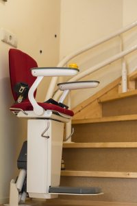 red cushion stair lift at the bottom of stairs