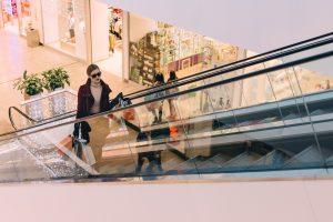 trendy woman shopping bags going up an escalator