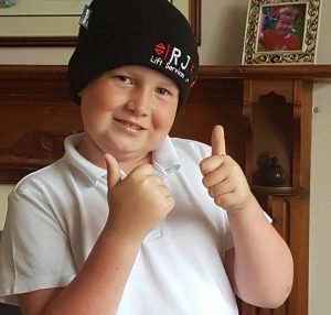 boy with RJ hat on and thumbs up