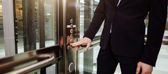 Man pressing lift button - R J Lift Services
